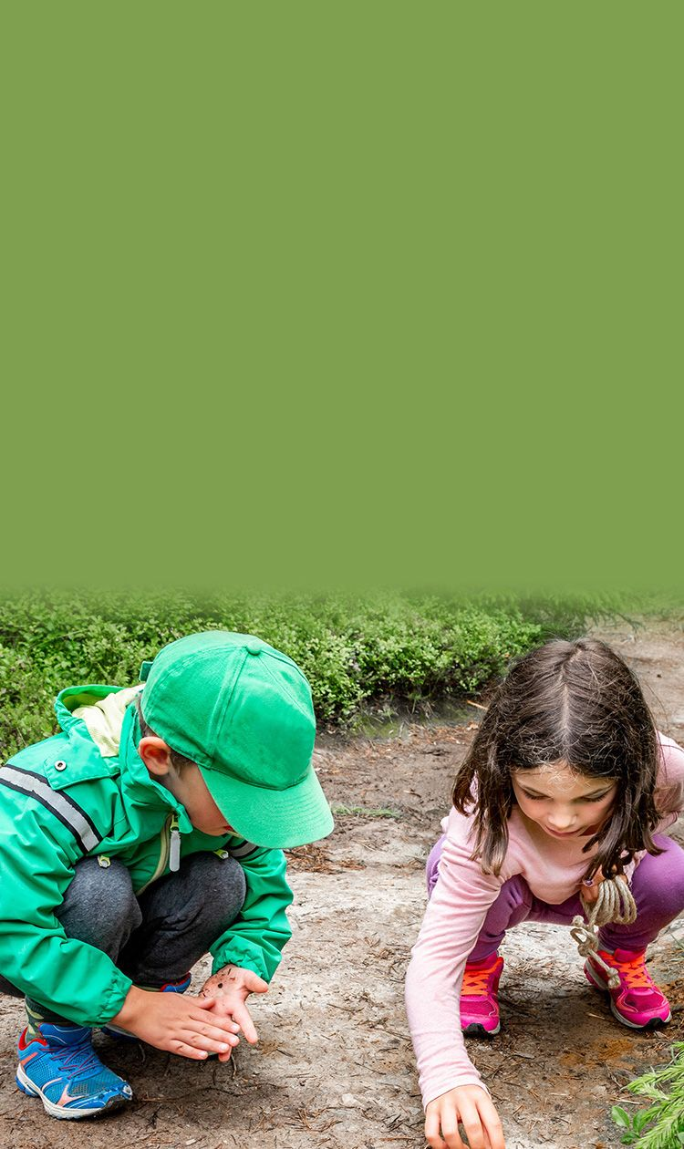 boy and girl sitting on forest ground exploring and learning about nature and insects. Looking at a black bug.