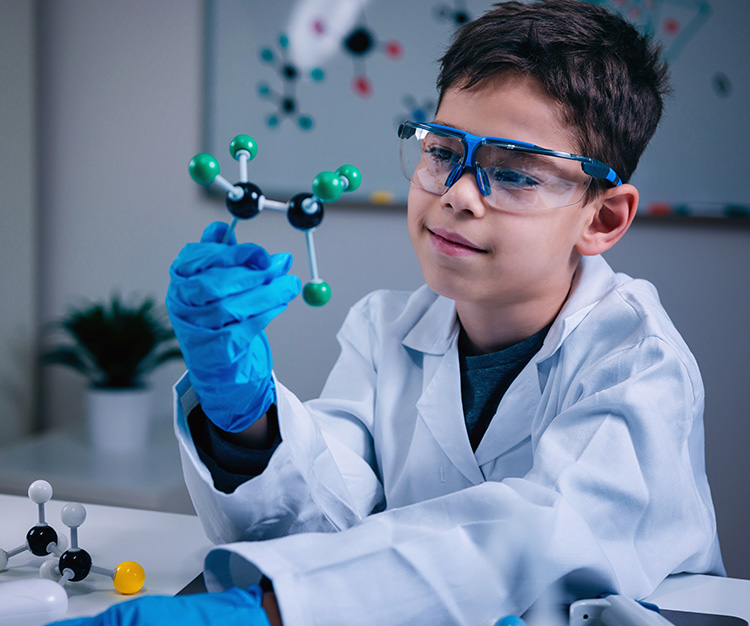 boy holding molecular model in a lab coat wearing rubber gloves and safety goggles