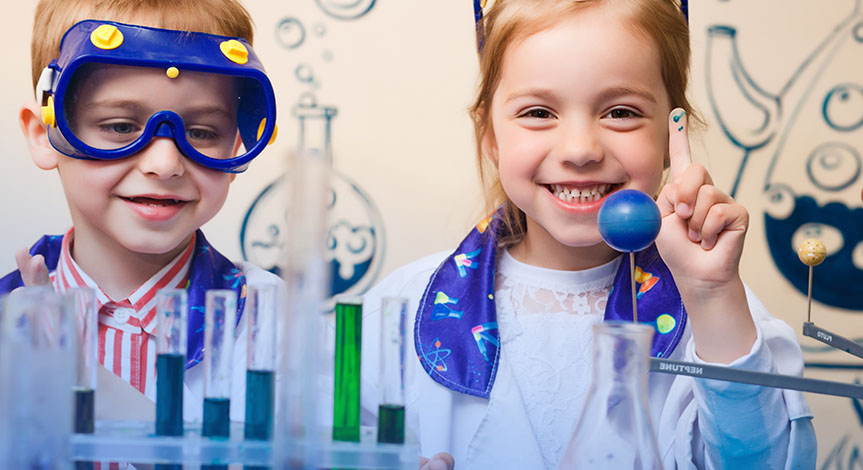 boy and girl standing behind table fll of test tubes.  The girl is holding her finger in the air to show the blue paint her h