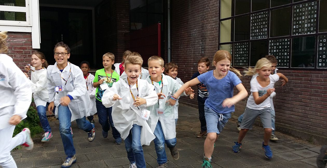 Kids in mad science lab coats running out of school