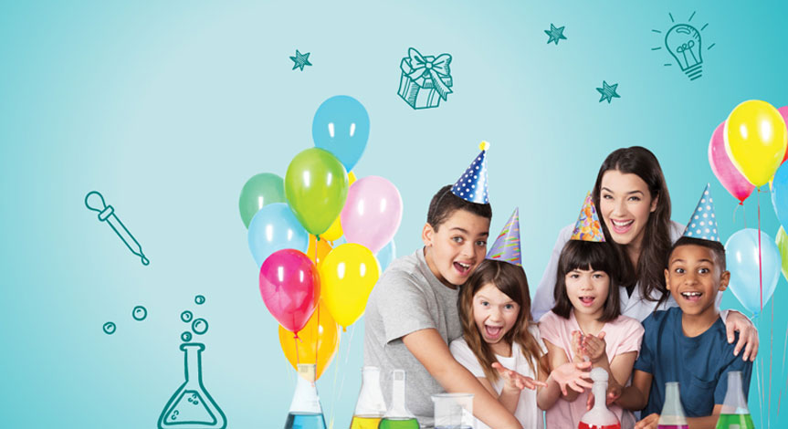 4 kids celebrating a birthday party with balloons and birthday hats.  Female scientist smiling in back of children